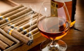 cuban cigar and bottle of cognac on wood background