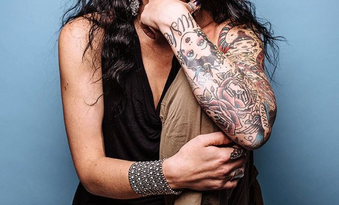 Studio portrait of beautiful model on blue background, long hair and blue eyes and tattoos.